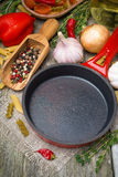 Empty frying pan, vegetables and spices on wood background Stock Image