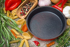 Empty frying pan, vegetables and spices on wooden background Royalty Free Stock Images