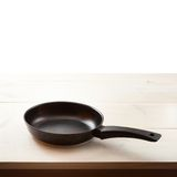 Empty frying pan on wooden background. Royalty Free Stock Photography