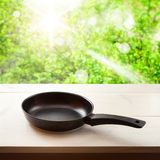 Empty frying pan on wooden background. Stock Photography