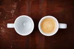 Empty and full cup of fresh coffee on rustic wooden table, benefits and harms of coffee concept Stock Image