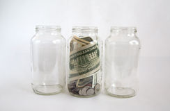 Empty and full of money glass jars Royalty Free Stock Photos