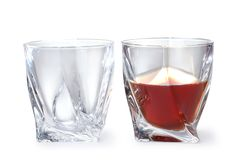 Empty and full whiskey glasses on white stock photography