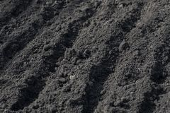 .Empty furrows on black ground in a farm field in early spring. Preparation of soil for planting seeds. Horizontal photography. Empty furrows on black ground in stock photos