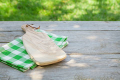 Empty garden table with cutting board over tablecloth Stock Photo