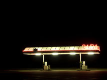 Empty Gas Station at Night. An empty gas station at night. It looks creepy. A few neon lights are on. We can guess a parking lot on the foreground Stock Photos