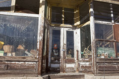 Empty General Store front. The old merchandise and grocery store has been closed for many years.  The seasons have weathered the wooden framing around the dirty Royalty Free Stock Images