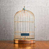 Empty gilded cage. Empty bird golden cage on the table Royalty Free Stock Images