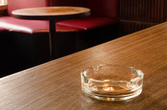 An empty glass ashtray on a table in a cafe. An empty glass ashtray lying idle on a bar counter in a cafe with the venue's interior being visible in the Royalty Free Stock Images