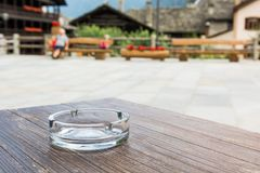Empty glass ashtray on a wooden table. At public square Royalty Free Stock Photos