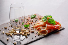 An empty glass, basil leaves, pistachios and red sliced ham on a light gray background. Tasty snacks for an alcoholic Royalty Free Stock Images