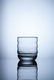 Empty glass on blue light background Stock Images