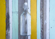 Empty glass bottle against multi colored wooden Stock Photography
