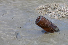 Empty glass bottle on the beach Royalty Free Stock Image
