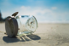 Empty glass bottle on sandy beach with blue sky and sea Royalty Free Stock Photos