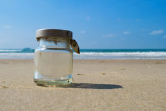 Empty glass bottle on sandy beach with blue sky and sea Stock Photo