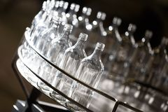 Empty glass bottles on the conveyor. Factory for bottling alcoholic beverages royalty free stock photography
