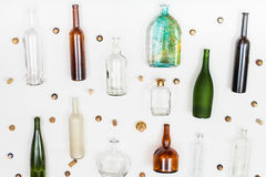 Empty glass bottles and corks arranged on white Royalty Free Stock Images