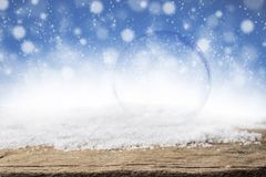 Empty glass bubble on Christmas snow and wood background. Empty glass bubble ball on Christmas snow and wood background. Frost snow and wooden desk space Royalty Free Stock Images