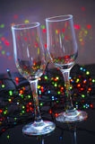 Empty glass champagne glasses. On a background of festive colored lights Stock Photos