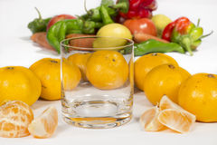Empty glass cup next to several mandarins and tangerine segments Stock Photos