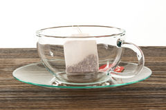 Empty glass cup with a tea bag on a wooden table, isolated on wh Stock Image