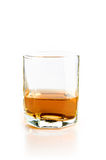 Empty glass with flowing whiskey. Isolated on white Royalty Free Stock Photo