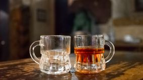 An empty glass and a glass of brandy. Glass glasses. Half empty. Half full. Different people. Romantic date. Philosophy of dissimilarity royalty free stock photo
