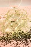 Empty glass goblets for champagne in golden confetti on the table. Festive background. Party concept royalty free stock images