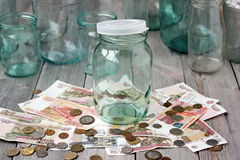 Empty glass jar and Russian money on the wooden table. Royalty Free Stock Photography