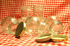 Empty Glass Jars. This photo shows several mini empty glass jars on a red gingham background Stock Image