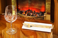 Empty glass, knife and fork on table. Empty glass, knife and fork on white napkin at table in restaurant; coals smolder in fireplace royalty free stock photography