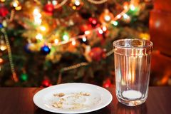 Empty glass from milk and crumbs from cookies for Santa Claus un. Der the Christmas tree with lights, close-up Royalty Free Stock Photography