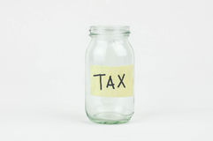 Empty glass money jar with tax label, financial concept. Stock Photography