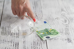 Empty glass and one hundred Euro banknotes on wooden table Stock Photos