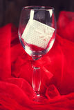 Empty glass with small gift box inside and around Royalty Free Stock Images