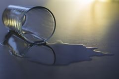 An empty glass, with spilled water, lies on a gray table. Close-up Stock Photo