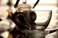 Empty glass and teapot. On the reflected background royalty free stock images