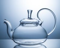 Empty glass teapot on a gray background stock photos