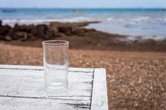 An empty glass of water is on white wooden table at beach Stock Photography