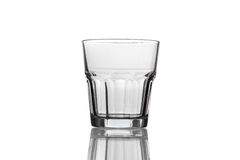 Empty glass for whiskey on a reflective surface. Stock Photos