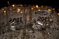 An almost empty glass of the year 2018 and another full of the new year 2019 stock photos