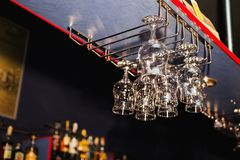 Empty glasses of alcohol hanging on the bar Royalty Free Stock Image