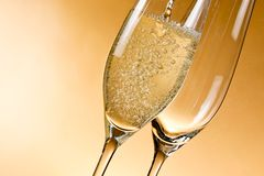 Empty glasses of champagne and one being filled Royalty Free Stock Images