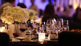 Empty glasses of champagne softdrink, soda and wine on Gala Dinner table. Candle light up with flower bouquet and background of people dancing, blurred stock video