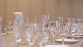 Empty glasses for champagne, wine and vodka set on a festive table in a restaurant, focus shift of glassware. Table decoration stock video