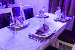 Empty glasses and dishes set in an interior new luxury restaurant with covered tables Royalty Free Stock Photo