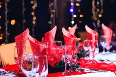Holiday red decorations in restaurant. Empty glasses set with red holiday decoration and bokeh background. royalty free stock photo