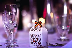 Romanian holiday decorations in restaurant. Empty glasses set with Romanian symbol of tricolor and bokeh background. stock photos