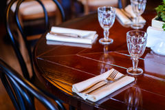 Empty glasses set on wooden table at restaurant. Dining table served forks, knives, glasses, napkins. Flowers in the center of the table stock photo